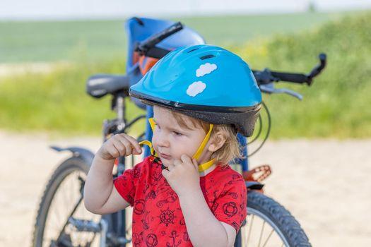 Lttle boy adjusts his safety helmet