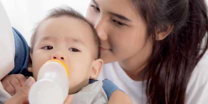 Young asian mother embracing and feeding little baby girl with bottle of milk at home, newborn innocence drinking with mom satisfied, relationship and bonding of mum and child, family concept.