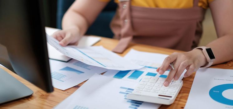 woman accountant making working audit and calculating expense financial annual financial report balance sheet statement, doing finance making notes on paper checking inspection.