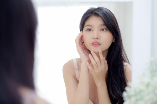 Beautiful young asian woman smiling look at mirror of checking face with skin care and cosmetic for rejuvenation and hygiene, beauty girl happy clean facial with cream or lotion and for health.