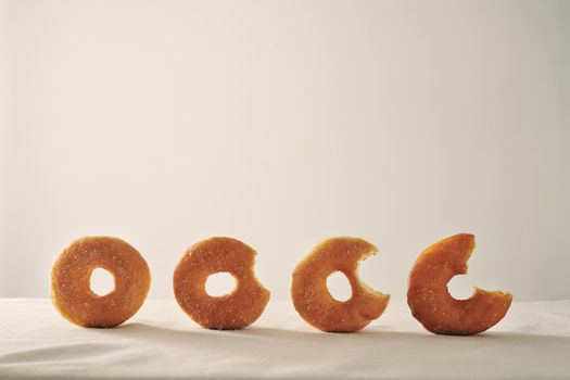 Donuts sprinkled with powdered sugar on linen tablecloth