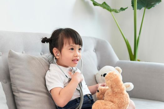 A doctor girl playing and cure bear at the pediatric