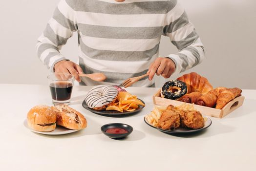 Man with multiple type of Fast food. Unhealthy food concept