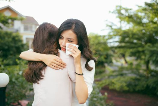 Portrait two women. Sad unhappy young woman being consoled by her friend. Friendship help support and difficult times concept. Human emotions feelings