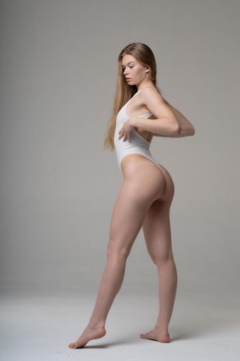 young beautiful woman posing in a white bodysuit in the studio