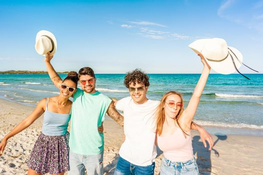 Group of gen z friends embracing to each other looking at camera on the seashore in tropical ocean resort. Happy students enjoying sea vacations together. Carefree people posing for photography