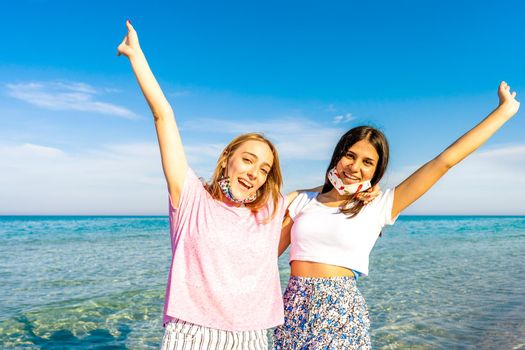 Two happy gen z girls embracing to each other with raised open arms looking at camera wearing funny protective open face mask enjoying sea vacations with crystal sea water and blue sky in background
