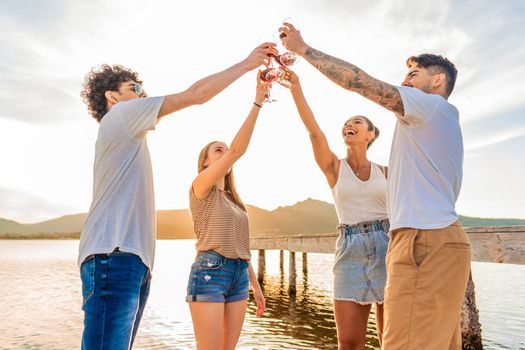Group of multiracial happy friends toasting at the beach with red wine at sunset clinking glasses in front of sunlight in backlit. Young people having fun in outdoor party drinking alcohol together