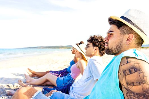 Selective focus portrait of handsome hipster guy with tattooed arm in white Panama hat sitting on seashore with friends looking at ocean water in vacation resort. Modern young people enjoying travel