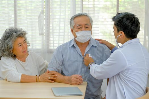 The doctor check up to old man at home with his wife who look worry about health.