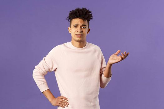 So what, why asking. Portrait of unbothered and careless, ignorant young man dont care on people rules, raising hand in dismay and confusion, being puzzled, look uninterested, purple background