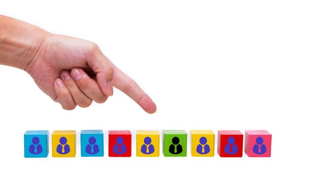 Hand pointing at a wooden block one leader person represented by icon.