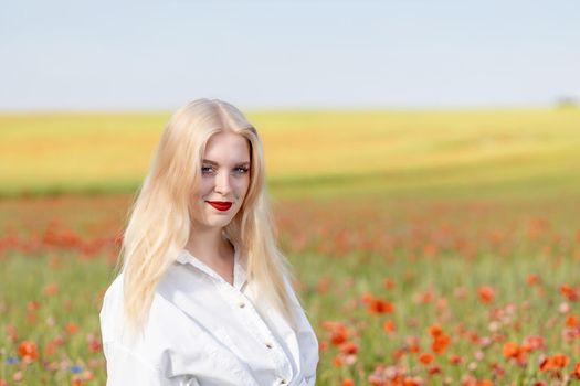 Smiling blonde girl is  posing in red poppy field.