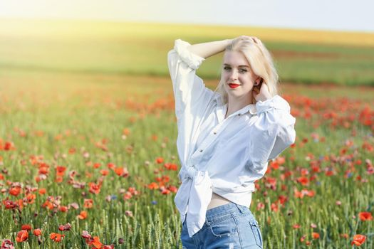 Attractive young girl posing in a field with red poppies.