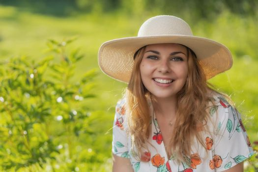 Smiling attractive  young woman in straw hat posing outdoors.