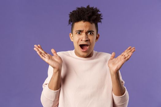 Close-up portrait of displeased, bothered frustrated hispanic man spread hands sideways in dismay and confusion, staring camera upset with disappointed grimacing expression, purple background