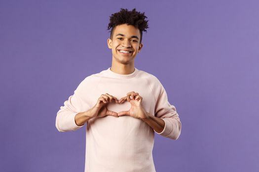Portrait of young happy, romantic lovely boyfriend express his love and sympathy to dearest person, show heart sign and beaming smile, like this girl and trying to confess feelings, purple background