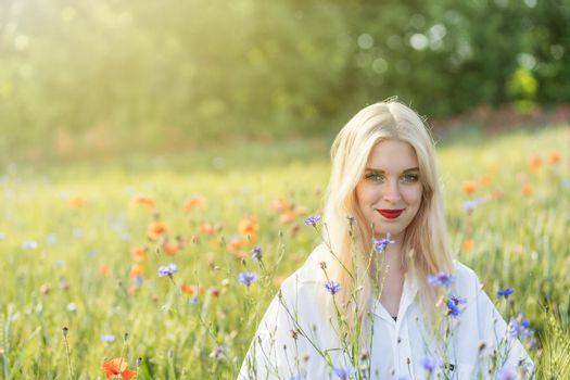 Blonde young woman posing in summer flower meadow.
