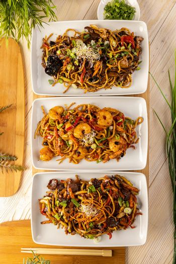 Three plate with stir fry noodles.