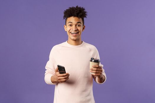 Waist-up portrait of happy enthusiastic hispanic man with smartphone, hold mobile phone and drinking coffee from take-away cup in office cafe, discuss recent project coworkers and team