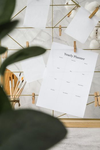 YEARLY PLANNER cards and posters mock ups on grid board. Copy space. Home office desktop. Freelance bloggers workplace. Brushes and palette