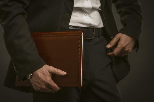 Successful businessman holds documents folder. Good looking caucasian man in formal wear holding brown leather document folder. Close up shot. Paperwork concept. Toned image