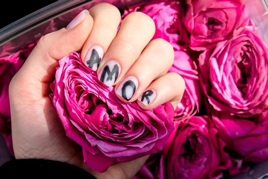 AMOR word on nails manicure hold Pink rose flower. Minimal flat lay nature. Female hand. Love