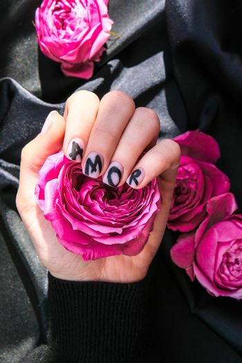 AMOR word on nails manicure hold Pink rose flower on black silk fabric. Minimal flat lay nature. Female hand. Love