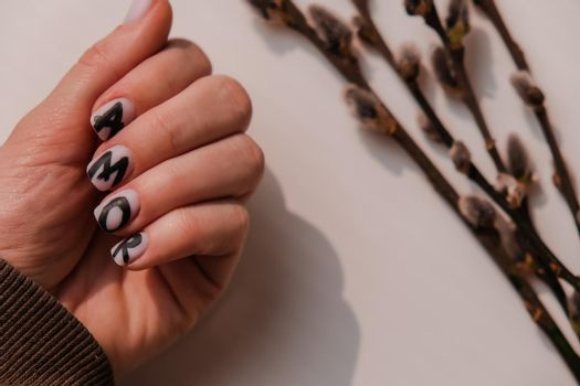AMOR word on nails manicure. Minimal flat lay nature. Female hand. Love. Skin care. Self care at home