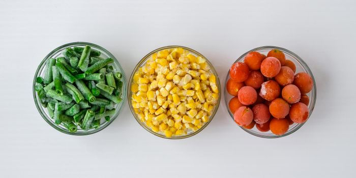 Three Bowls of frozen vegetables food of yellow corn, green beans, red tomatoes. Colors of traffic light. Harvest Food preservation for winter.