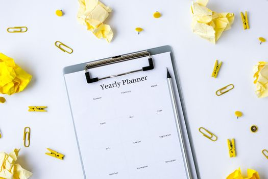 Yearly goals planner on white background. Planning year to stay productive when working from home during quarantine period. Alarm clock pen