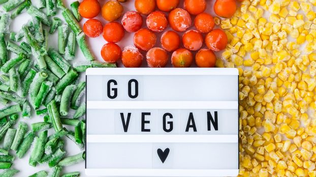 Lightbox with text GO VEGAN frozen vegetables food of yellow corn, green beans, red tomatoes. Colors of traffic light. Harvest Food preservation for winter.