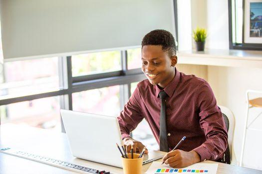 Black man watching educational webinar on laptop, studying, preparing for exam, talk in video chat