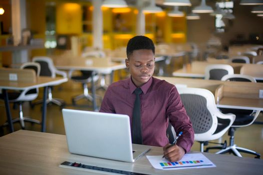 portrait of contemporary African-American man using laptop sitting at table in coffee shop, copy space