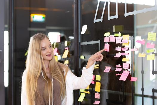 Young women sticking post-its on an idea board. Brainstorming and organizing, whiteboard, chalkboard