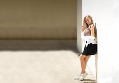 Portrait of young beautiful woman blonde hair standing against wall with copy space
