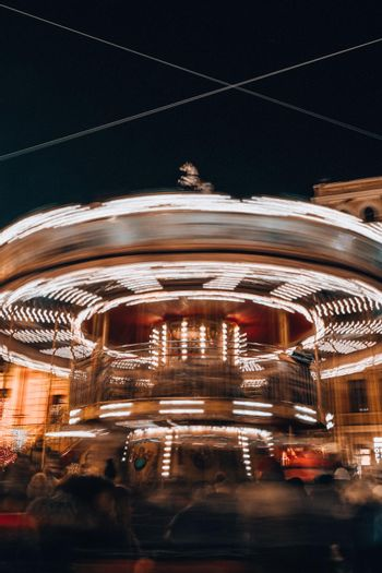 Children's Carousel in the evening and night illumination. Spinning retro carousel. Merry-go-round at night motion blur as the light streak in a circle