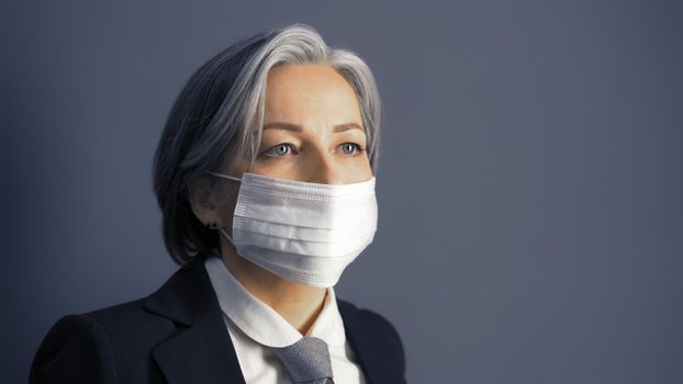Gray haired businesswoman in protective mask looking at side, Masked fashion Caucasian woman in formal wear isolated on gray background. Epidemic concept