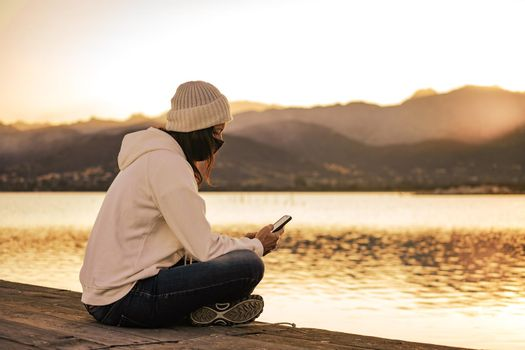 Unrecognizable young woman in white wool hat sitting on a pier alone wearing protective face mask using smartphone to keep in touch with friends and family due to Coronavirus social distancing