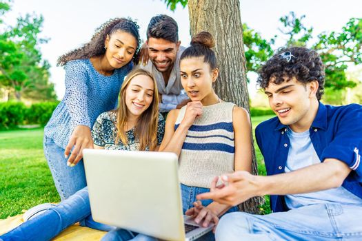 Young hipster friends group sitting on grass in city park making surprise faces looking laptop screen. Modern fun concept with millenials on new trends and technology. Wireless and social media
