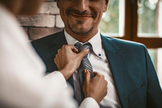 Businesswoman Straightens A Tie To Well Dressed Man
