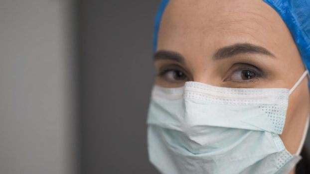 Female Medic In Protective Mask Looks At Camera