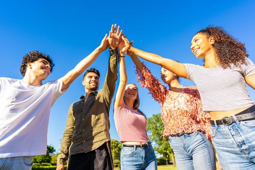 Group of happy gen z friends touching hand raised up to each other. Concept of trust in future and success in life. Diverse millenial multi ethnic students bonding outdoor in nature of city park