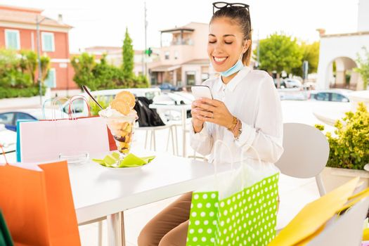 Happy young woman resting with open protective face mask sitting at a bar outdoor among several colored paper bag to eat ice cream after shopping in city center. Girl using smart phone to buy online