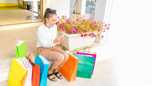 Happy young woman resting with open protective face mask after shopping in city center sitting among several colored paper bag. Millenial modern person using smart phone to buy and deals online