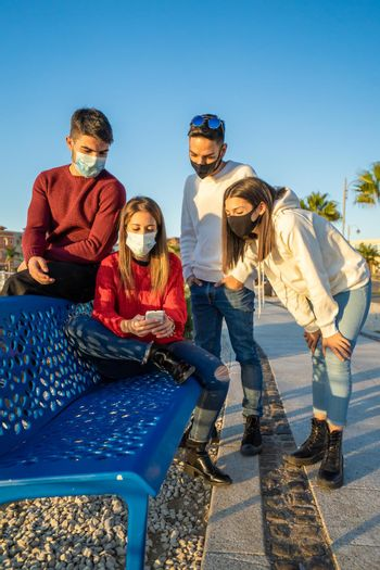 Millenial friends using smart phones wearing protective face mask on Covid wave. Worried guys and girls watching news on mobile smartphone. Travellers group stay in touch during pandemic in vacations