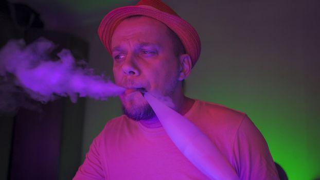 Smoker Of Hookah Exhales Smoke In Neon Backlit