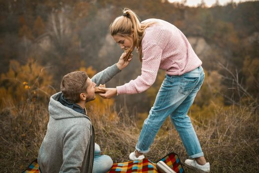 Man And Woman Feed Each Other Sandwiches Outdoors