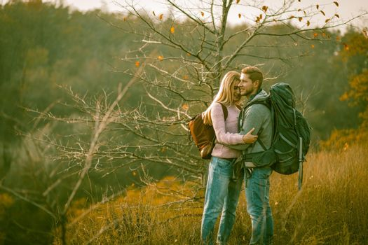 Happy couple admires of nature standing with backpacks on autumn grass. Young Caucasian man and woman smile embracing while enjoying the beautiful view. Togetherness with nature concept