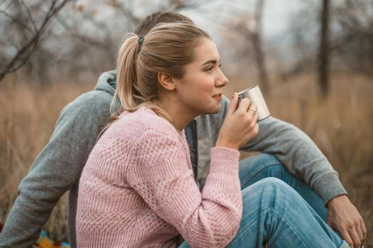 Picnic in nature. Young woman and man rests drinking hot coffee or tea while sitting on blanket at autumn grass outdoors. Profile view. Lifestyles concept